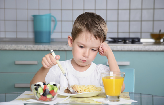 sad little boy sits at the dining table and looking in the plate. horizontal