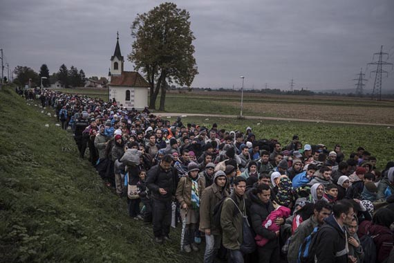 Migrants walk past the temple as they are escorted by Slovenian riot police to the registration camp outside Dobova, Slovenia, Thursday October, 22, 2015. The small Balkan nations on the path of the human migration through Europe are seeing record numbers of asylum-seekers cross their borders, and are overwhelmed in their ability to manage the human flow. Despite hopes that plummeting temperatures and treacherous seas would finally slow the tide of refugees flowing into the heart of Europe, fresh fighting in Syria and growing fears of border closings are driving more migrants to undertake the treacherous trek.