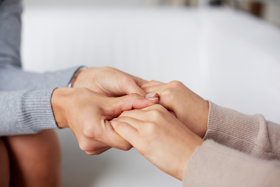 Close-up of psychiatrist hands holding those of her patient