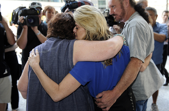 Sharon Tomlinson (centre), and a woman who cannot be identified (left), both alleged victims of serial rapist Robert Fardon hug outside the Supreme Court in Brisbane, Friday, Sept. 27, 2013. Robert John Fardon, 63, who has been serving an indefinite sentence for sex offences, is to be released from jail into the community, under supervision. (AAP Image/Dan Peled) NO ARCHIVING