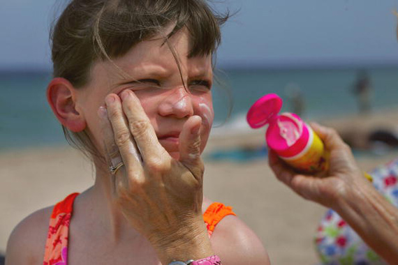 FORT LAUDERDALE, FL - JUNE 20: Sharon Doyle puts sunscreen on the face of 9-year-old Savannah Stidham as they visit the beach June 20, 2006 in Fort Lauderdale, Florida. Recent studies have shown that the best way to protect against melanoma from the sun is to use a sunscreen that includes zinc oxide, titanium dioxide or avobenzone. People exposed to the sun should look for water-resistant sunscreen with a Sun Protection Factor (SPF) of 30 or higher. (Photo by Joe Raedle/Getty Images)