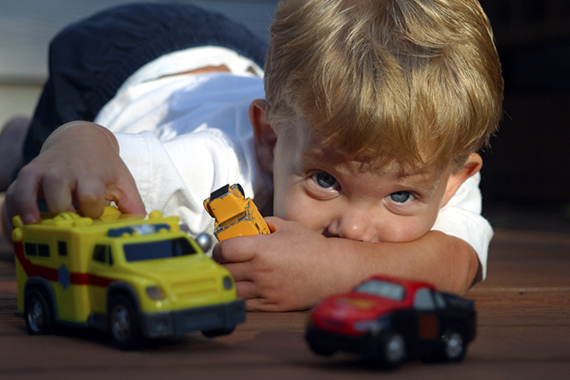 Caucasian Boy Playing With Toy Trucks On The Floor