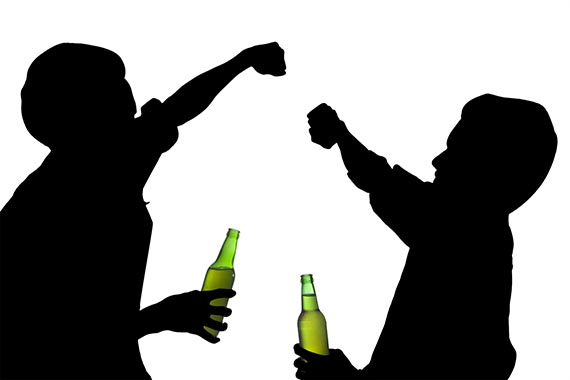 Silhouette drunk men fights while holding a bottle of beer