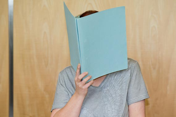 Defendant Andrea G. , who is accused of murder, covering her face with a folder, in the court room of the regional court in Coburg, Germany, Tuesday July 12, 2016. A couple have gone on trial in Germany after the remains of eight babies were found at their apartment in Bavaria last year. The 45-year-old mother, identified only as Andrea G., is charged with four counts of murder in the trial at the Coburg state court and her 55-year-old husband, Johann G., with being an accessory to murder. (Daniel Karmann/dpa via AP)