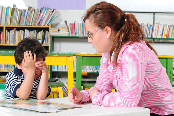 Preschool teacher sitting with student in a classroom.